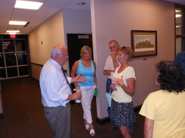 Shorewood Mayor Rick Chapman, who supports plans to build a gas station/car wash at U.S. 52 and River Road, discusses the board's vote in favor of the project with residents after the meeting.