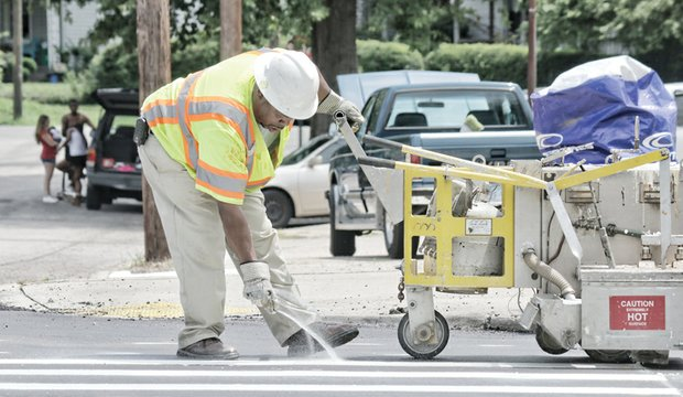 Antonio Hill, president of A&T Striping Co., puts the finishing touches on new roadway markings at a Richmond crosswalk. Location: Semmes Avenue and 34th Street on South Side. He and other companies have been called on to repaint markings on numerous streets. The city has been repaving many streets this year in preparation to host the international cycling championship in September.