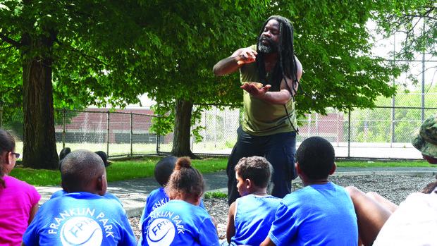 Ben Cunningham entertains children at a ReadBoston event in Marcella Park in Roxbury.