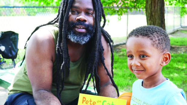 eller Ben Cunningham poses with Myles Esteves, who received a new book at a ReadBoston event in Marcella Park in Roxbury.