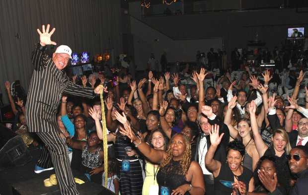 Michael Blair, the flamboyant MC for the SportsBall, strikes a pose with the crowd that packed Minglewood Hall. (Photos: Warren Roseborough)