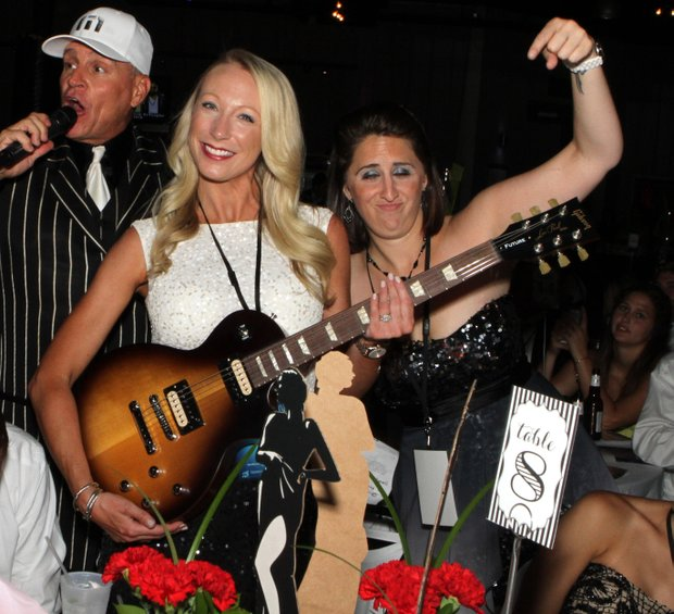 Kelly Jordan proudly holds up her guitar after she won it in the auction.