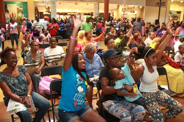 Audience members clamor to answer questions to win prizes at the Expo stage in front of Sears.