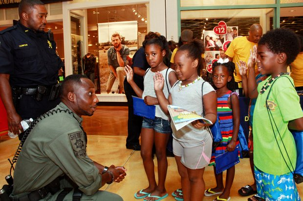 """A SWAT team member from the DeKalb County Sheriff's Office """"deputizes"""" students to stay in school and get good grades."""