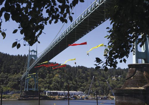 Environmental activists from Greenpeace unfurl colored banners while hanging from the St. Johns Bridge and kayakers join them below in ...