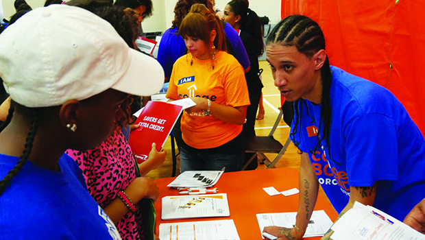 Alex Diaz explains College Bound Dorchester's programs to attendees at the city-sponsored  Youth Bank Day held July 27 at the Reggie Lewis Track and Athletic Center