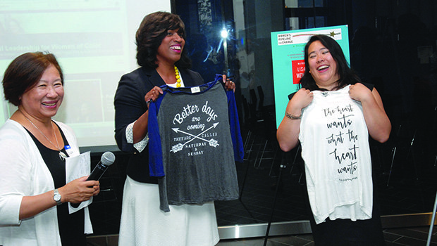Boston City Councilor Ayanna Pressley (c) presents Fitchburg Mayor Lisa Wong (r) with special T-shirts as part of honoring her accomplishments as the first Asian-American mayor, youngest female elected and one of few women mayors in the Commonwealth. Award-winning educator Suzanne Lee (l) looks on with admiration. Mayor Wong was celebrated by the Women's Pipeline for Change on the rooftop of the new Bruce C. Bolling Municipal Building in Dudley Sq., Roxbury.
