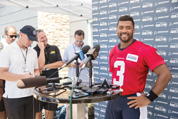 Seahawks quarterback Russell Wilson is all smiles at a training camp news conference last week following the announcement of successful negotiations extending Wilson's contract with Seattle through 2019.