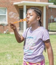 Tyleia Carter, 6, blows big bubbles saturday at the East End Get Fresh Fair and Farmers Market. The event was held on Accommodation street behind the Mosby Court Resource Center and offered a variety of nutritious vegetables and fruits for sale, as well as live music, games for children, health screenings and more.