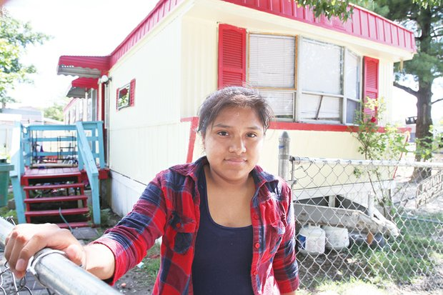 Olivia Leon Vitervo, standing in front of her family's mobile home at Rudd's Trailer Park last year, is a plaintiff in the lawsuit against the city.