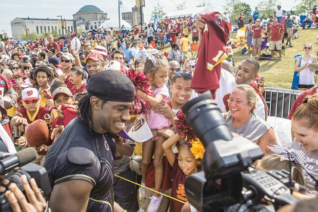 Washington quarterback Robert Griffin III, aka RGIII, greets well-wishers Saturday at Fan Appreciation Day at the team's training camp behind the Science Museum of Virginia. Clockwise from top right, Tatum Johnson, 7, gets a better look by riding the shoulders of her father, Bill Johnson.