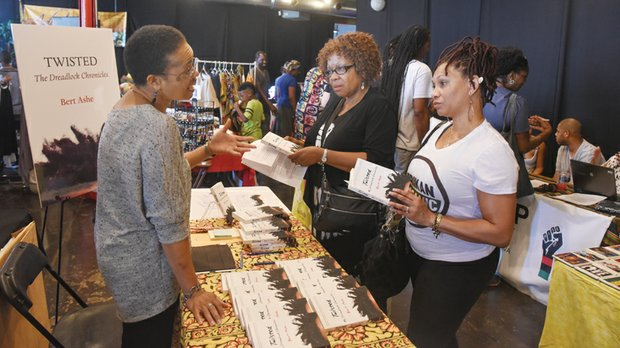 """Happily natural - Valerie Ashe, left, discusses her husband Bert Ashe's book, """"Twisted: My Dreadlock Chronicles,"""" with Gigi Garnett, center, and Dina Elliott last Saturday at the 13th Annual Happily Natural Day at Plant Zero on South Side."""