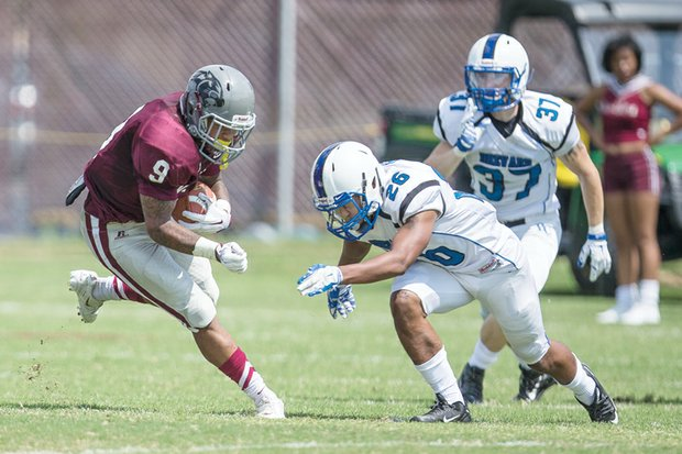 Virginia Union University freshman Hakeem Holland gets the ball past Brevard College opponents at Hovey Field, helping the Panthers to a 35-21 opening victory.