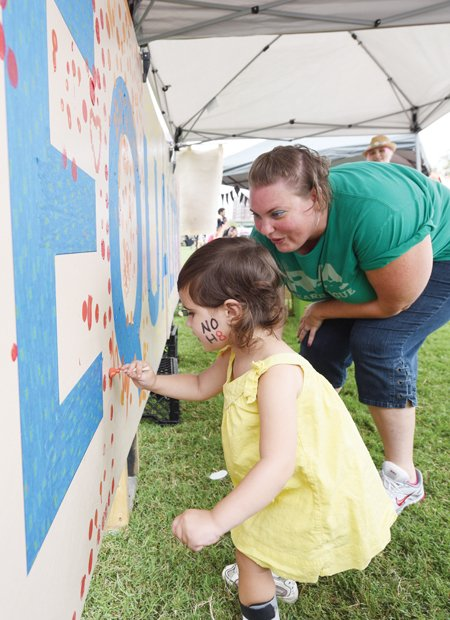 3-year-old Harper Tysall leaves her artistic mark on an equality mural with guidance from Amy Roberts.
