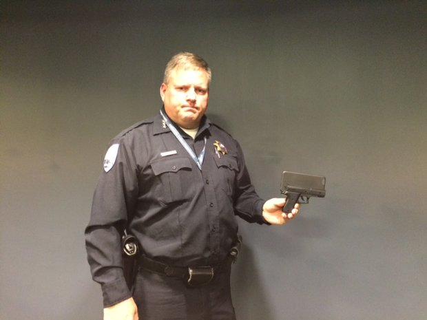 Plainfield Police Chief John Konopek displays a replica hand gun cell phone case.