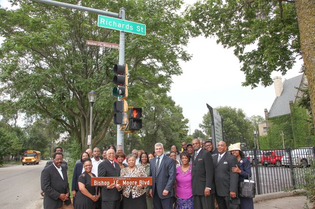 A crowd gathered around the sign post that now bears the name of Bishop J.E. Moore, who celebrates his 50th year as a pastor in Joliet this year.