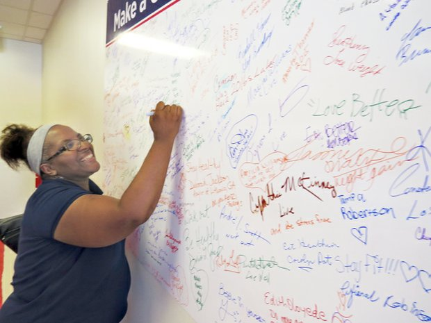 "LaJunne Smith signs the hospital's ""Wall of Health."""
