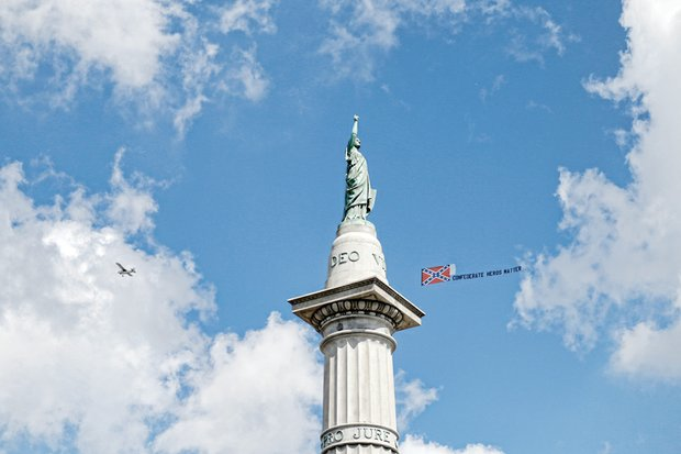"A plane flies above protesters at the Jefferson Davis monument on Monument Avenue with a trailing Confederate flag and a misspelled counter-protest message that ""Confederate Heros (sic) Matter."""