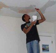A volunteer repairs the ceiling.