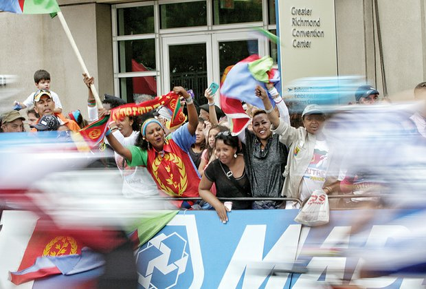 Fans from the African nation of Eritrea wave their country's flag as cyclists speed past them on Sunday during the Men's Elite Road Race.