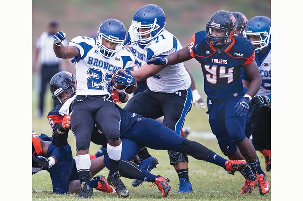 Virginia State University's Daryl Simmons, left, takes down the Broncos' Corbin Rascoe at Rogers Stadium in Ettrick last Saturday. The Trojans lost 33-20 to Fayetteville State University.