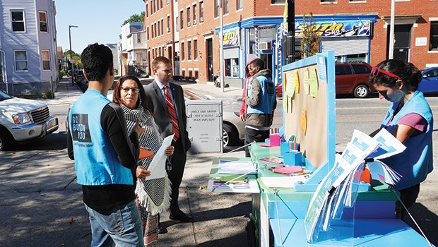 "A Go Boston 2030 representative discusses transportation ideas with Codman Square neighborhood resident Daisy Ramos at an ""Ideas on the Street"" pop-up cart in front of the Codman Square Library."