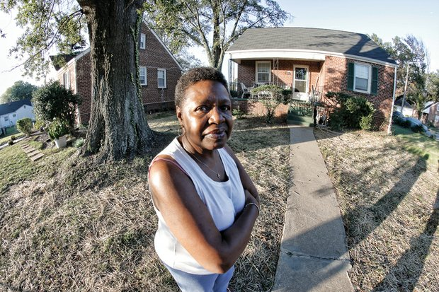 Charlene C. Harris stands in front of her two-bedroom home in the West End. She has been told to buy it or face having to move. Location: 1600 Colorado Ave.
