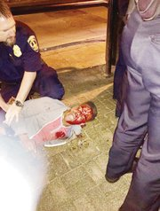 This photo taken by bystander Bryan Beaubrun shows the bloodied Martese Johnson as an officer holds down the University of Virginia honors student during his arrest March 18 outside a Charlottesville pub.