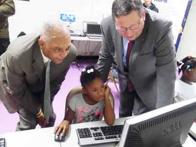 Dr. Gregory Thornton, CEO of Baltimore City Public Schools (left) and David L. Cohen, Senior Executive Vice President of Comcast Corporation (right) observes a student using the Internet at Towanda Community Center.