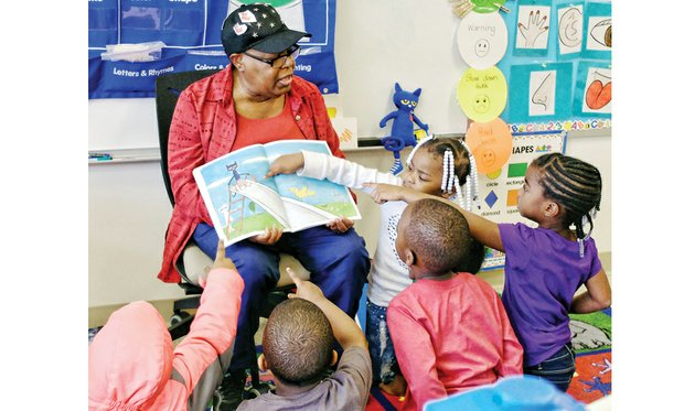 "Where's the cat? / Volunteer Inez Crews engages the attention and participation of pre-schoolers Tuesday at Dr. Martin Luther King Jr. Learning Center in the East End as she reads ""Pete the Cat: Rocking in My School Shoes."" The book is part of the monthly read aloud and share program sponsored by RVA Reads. Each youngster will get a new book each month to take home and read and share with their families. Story on A6."