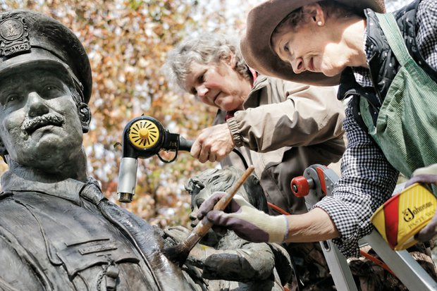 Lynda Solansky, left, and sculptor Maria J. Kirby-Smith clean the bronze Richmond Police Memorial statue in Nina F. Abady Festival Park beside the Richmond Coliseum.  Ms. Kirby-Smith created the 8½-foot-tall statue that was placed in 1987 and pays homage to city police officers and the 28 killed in the line of duty between 1869 and 2003. A private foundation paid for the statue that depicts an officer carrying a child down steps. The artist and her friend drove up from South Carolina to wash and wax the statue Tuesday, possibly the statue's first cleaning since it was dedicated 28 years ago.  The cleaning was done ahead of a wreath-laying ceremony that Mayor Dwight C. Jones will lead Tuesday, Nov. 24, according to retired Officer Glenwood W. Burley, the statue's protector. He's now leading a push to win city approval to move the statue from its home on the 7th Street side of the park to The Carillon area of Byrd Park.  The Carillon Civic Association, which represents people living next to the park, has publicly expressed opposition, arguing the statue would be out of place and urging city leaders to find a more suitable location.