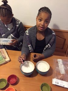 Kamilah Scott looks up as her twin sister, Nikayla Scott reads a package in preparation of making soap for their new business called Little Ladies Organics. The nine year olds will sell their products with fellow entrepreneurs ages seven to 30 at the Pip Moyer Recreation Center in Annapolis on Saturday, November 28, 2015.