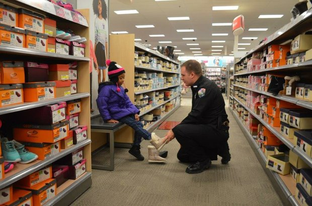 Shorewood police officer Adam Beaty helps Domineek, 5, try on a pair of new winter boots at the village's annual Shop with a Cop event.