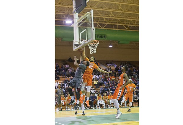 Virginia State University's Te'Quan Alers goes airborne to block the layup of Virginia Union University player Devin Moore at last Sunday's game at the Arthur Ashe Athletic Center.