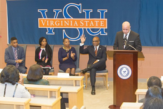 Dr. Makola M. Abdullah waves to the audience as Virginia State University Rector Harry Black introduces him last Friday as the university's new president. With him, from left, are son Mikaili, daughter Sefiyetu, and his wife, Dr. Ahkinyala Cobb-Abdullah.