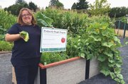Cindy Clemens shows some of the vegetables harvested last summer at Centennial Park Community Garden in southeast Portland, which raised 726 pounds of produce to help stock the food bank at Birch Community Services.