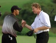 Tiger Woods greets Ernie Els on the 18th green of the Mercedes Championships in Kapalua, Hawaii, in January 2000, after they both sank eagle putts to force a playoff. At 24, Woods won on the second playoff hole for his fifth consecutive PGA Tour victory and the 14th of his young career.