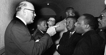 "Registrar Carl Golson shakes a finger at Dr. Martin Luther King Jr. during a meeting at the courthouse in Hayneyville, Alabama, March 1, 1965. King inquired about voter registration procedures but Golson told him that if he was not a prospective voter in Lowndes county, ""It's none of your business."" King visited two nearby counties after leading a voter registration drive in Selma."