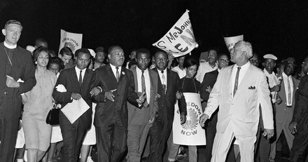 Dr. Martin Luther King, center, leader of the Southern Christian Leadership Conference, leads a parade of civil rights marchers from a rally in a church to Lafayette Park, opposite the White House in Washington, Aug. 5, 1965. The march capped two days of street corner rallies in Washington. On Aug, 6, the Voting Rights Act was signed into law by President Johnson, and King stated that he hoped to register 900,000 Blacks to vote in Southern states.