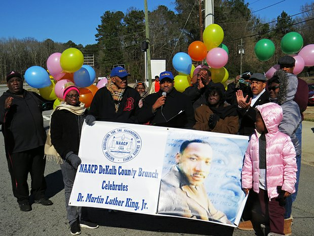 Rev Darryl Roberts welcomes marchers and spectators to the DeKalb NAACP's 14th Annual Martin Luther King Parade & Rally on Jan. 18, 2016. DeKalb NAACP President John Evans is on his immediate right. On his left are parade Grand Marshall Sarah Copelin Wood and Associate State Court Judge Ronald Ramsey is on his left.