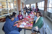 Volunteers from the Alpha Kappa Alpha sorority help make care packages for the troops.