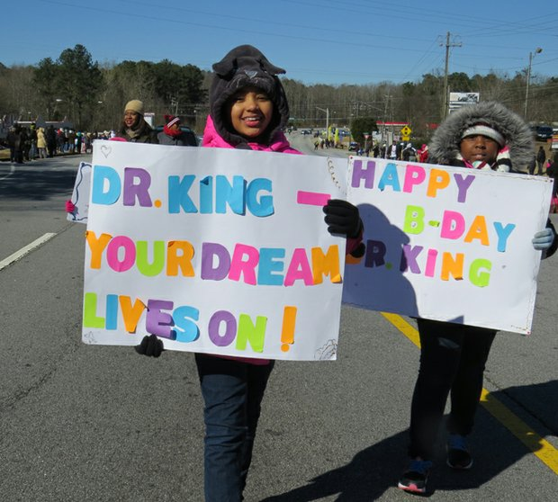 Celebrating King Day: young marchers at DeKalb NAACP parade (above), volunteers repairing a senior's home (below), Kaiser Permanente employees at Lou Walker Center, and activists at Rock of Ages packaging rice for refugees.