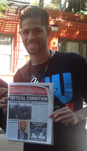 Michael J. Feeney holding the New York Amsterdam News at the African American Day Parade.