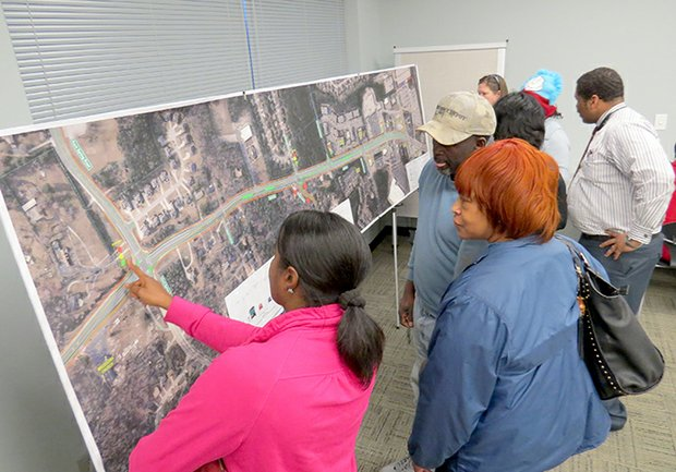 Stacey Thibodeaux (in pink), who has lived off Browns Mill Road for 14 years, looks over the Panola Road project on Feb. 22 at the Salem-Panola Library in Lithonia.