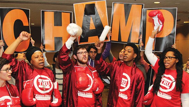 "TRU protesters, dressed as boxers representing solutions that fill the MBTA budget gap without raising fares, urge the FMCB to ""be a champ, not a chump"" and vote against fare increases."