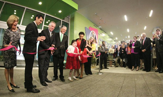 Gov. Terry McAuliffe, third from left, cuts the ribbon at the grand opening ceremony Wednesday. Joining him, from left, Leslie Wyatt, executive director of the Children's Hospital; VCU President Michael Rao; John DuVal, CEO of VCU Health Systems; Brianna Burke and her mother, Nicole Hauser; and Maggie Raph holding her son, Carter.