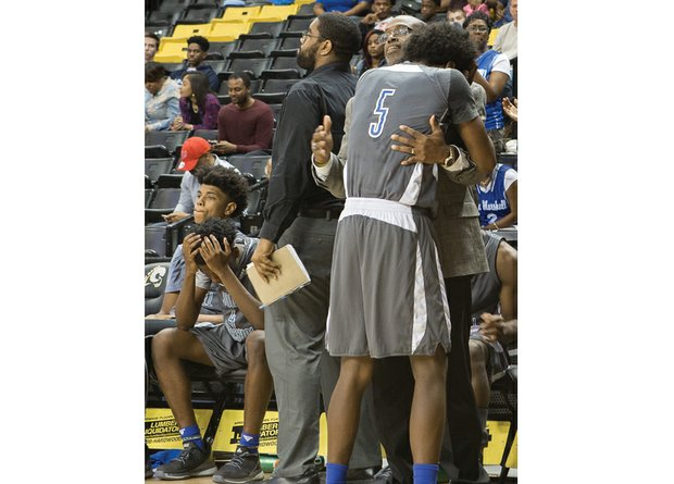 John Marshall High's Xavier Trent seeks consolation from Assistant Coach Kevin Bettis in the late stages of the Justices' 75-62 loss to Portsmouth's I.C. Norcom High School in the State 3A semifinals last Friday at the Siegel Center at Virginia Commonwealth University.