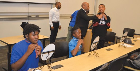 "Mentors in the 100 Black Men of Los Angeles Mentoring Program held at West Los Angeles College, taught a group of young men how to tie bow ties at the end of its ""Power of Brotherhood and Entrepreneurship"" seminar on Saturday. The young men were taught the power of having the right circle around them and that it's never too early to start your own company."