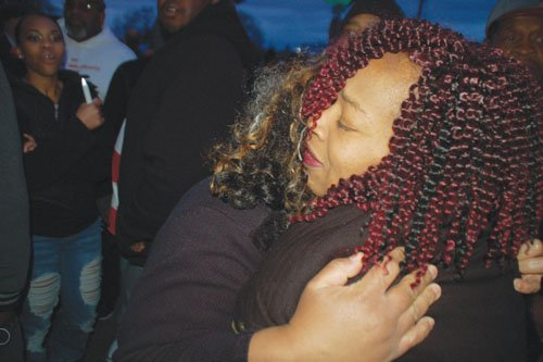 Shelly Curry is embraced during the community vigil in honor of her late husband.
