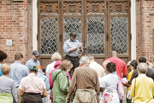The Rev. Paul A. Coles, pastor of Sharon Baptist Church, leads a reading from the Easter story outside Centenary United Methodist Church on Grace Street, one of the stops on the Stations of the Cross walk last Friday.